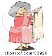 Gray Haired Lady In An Apron Holding Up A Clean Beige Towel