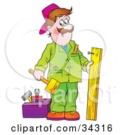 Poster, Art Print Of Friendly Male Handyman In Green Hammering A Nail Into A Wooden Board