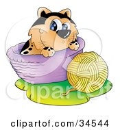 Clipart Illustration Of A Playful Spotted Orange Cat In A Basket Playing With A Ball Of Yarn