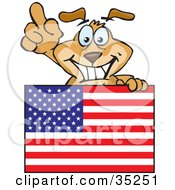 Friendly And Smiling Brown Dog Pointing Up And Standing Behind An American Flag