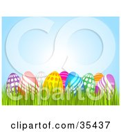 Clipart Illustration Of A Group Of Colorful Polka Dot And Wave Patterned Easter Eggs Nestled In Grass Under A Blue Sky