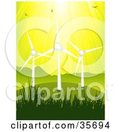 Birds Flying In Sunshine Above Three Wind Turbines On A Green Grassy Hill Against A Yellow Sky