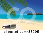 Pair Of Sunglasses Resting Under A Palm Tree On A Tropical Sandy Beach With Huts On The Water In The Background