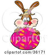 Clipart Illustration Of A Hungry Bunny Rabbit Licking His Lips And Touching A Pink Easter Egg With Carrot Patterns On It