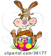 Clipart Illustration Of A Bunny Rabbit With His Butt Stuck In A Broken Easter Egg