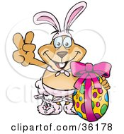 Clipart Illustration Of A Dog Wearing Bunny Ears And Slippers Signaling The Peace Sign And Standing With An Easter Egg