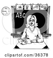 Clipart Illustration Of A Friendly Female Teacher Reading A Book At Her Desk In A Class Room