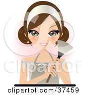 Pretty Brunette Maid In An Apron Holding A Feather Duster