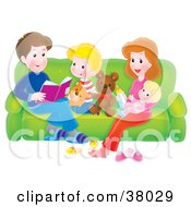 Father Reading A Story To His Children And Wife As They Relax On A Couch