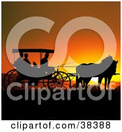 People In A Horse Drawn Carriage Silhouetted Against An Orange Sunset
