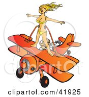 Pilot Flying An Orange Biplane While A Female Wingwalker In A Bikini Stands On The Wings