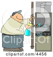 Man Spraying A Cleaning Solvent On A Standard Household Furnace