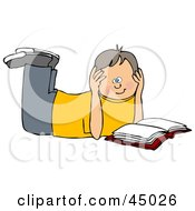 Boy Laying On His Belly And Reading A Book Resting His Head In His Hands