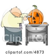 Businessman Carving A Halloween Pumpkin With A Knife
