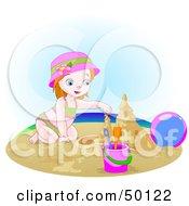 Small Girl Building A Sand Castle On A Beach