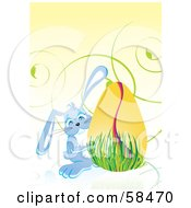 Royalty Free RF Clipart Illustration Of A Cute Blue Easter Bunny Peeking Around A Golden Egg In Grass by MilsiArt