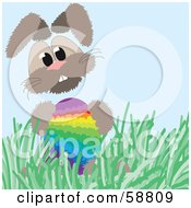 Bunny Rabbit In Grass Holding A Rainbow Easter Egg