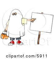 Boy Wearing A Halloween Ghost Costume While Pointing At A Blank Sign