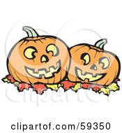 Two Carved Halloween Pumpkins Resting On Autumn Leaves