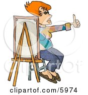 Female Painter Sitting Behind A Canvas While Holding Her Thumb Up