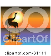 Royalty Free RF Clipart Illustration Of Two Silhouetted Cranes Wading In Water Against An Orange Sunset