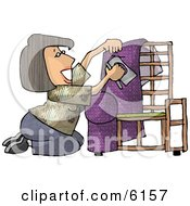 Woman Kneeling While Putting Purple Upholstery On A Chair Frame