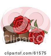 Two Red Roses Resting On Chocolate Hearts
