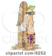 Blond Male Surfer Dude Polishing His Surfboard On A Beach
