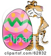 Royalty Free RF Clipart Illustration Of A Tiger Character School Mascot With An Easter Egg by Toons4Biz