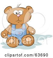 Stuffed Teddy Bear Sitting And Wearing Blue Overalls
