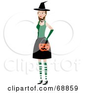 Young Woman Dressed In A Green And Black Halloween Witch Costume