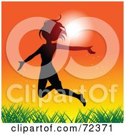 Silhouetted Woman Leaping Over Grass Against An Orange Sunset