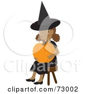 Happy Black Girl In A With Costume Sitting And Holding A Halloween Pumpkin