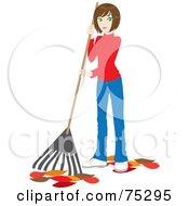 Brunette Caucasian Woman Raking Up Autumn Leaves In Her Yard