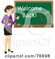 Brunette Caucasian Female School Teacher Pointing To A Chalk Board With Welcome Back And An Apple