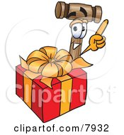Clipart Picture Of A Mallet Mascot Cartoon Character Standing By A Christmas Present by Toons4Biz