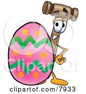 Mallet Mascot Cartoon Character Standing Beside An Easter Egg