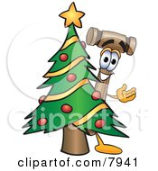 Clipart Picture Of A Mallet Mascot Cartoon Character Waving And Standing By A Decorated Christmas Tree by Toons4Biz