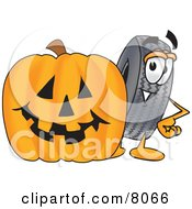 Rubber Tire Mascot Cartoon Character With A Carved Halloween Pumpkin