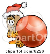 Clipart Picture Of A Cardboard Box Mascot Cartoon Character Wearing A Santa Hat Standing With A Christmas Bauble by Toons4Biz