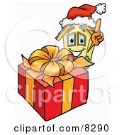 Clipart Picture Of A House Mascot Cartoon Character Standing By A Christmas Present