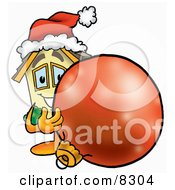 Clipart Picture Of A House Mascot Cartoon Character Wearing A Santa Hat Standing With A Christmas Bauble