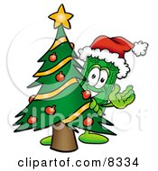 Dollar Bill Mascot Cartoon Character Waving And Standing By A Decorated Christmas Tree by Toons4Biz