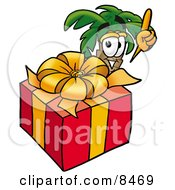 Palm Tree Mascot Cartoon Character Standing By A Christmas Present by Toons4Biz