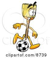 Broom Mascot Cartoon Character Kicking A Soccer Ball