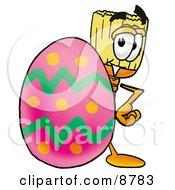 Broom Mascot Cartoon Character Standing Beside An Easter Egg