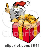 Clipart Picture Of A Camera Mascot Cartoon Character Standing By A Christmas Present by Toons4Biz