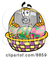 Clipart Picture Of A Camera Mascot Cartoon Character In An Easter Basket Full Of Decorated Easter Eggs