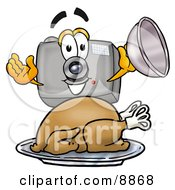 Clipart Picture Of A Camera Mascot Cartoon Character Serving A Thanksgiving Turkey On A Platter by Toons4Biz