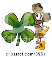 Wooden Cross Mascot Cartoon Character With A Green Four Leaf Clover On St Paddys Or St Patricks Day